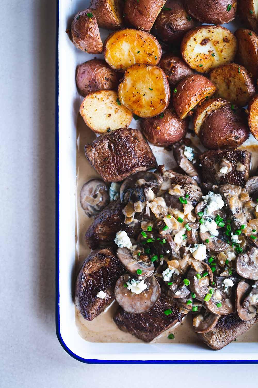 Steak tips, mushrooms, blue cheese sauce and potatoes on a sheet pan