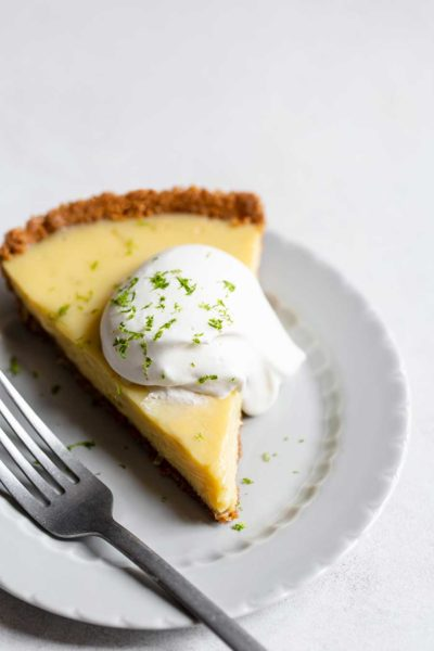 A slice of key lime pie topped with whipped cream