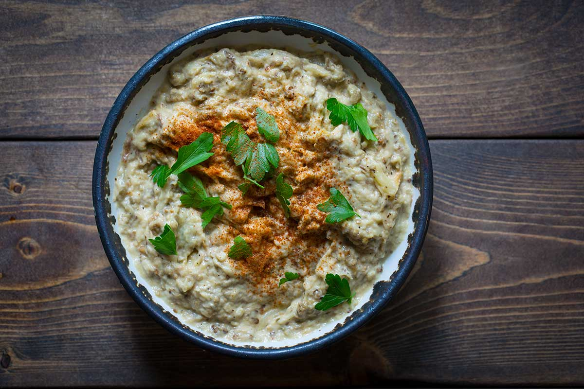 Baba Ghanouj in bowl, garnished with parsley and smoked paprika