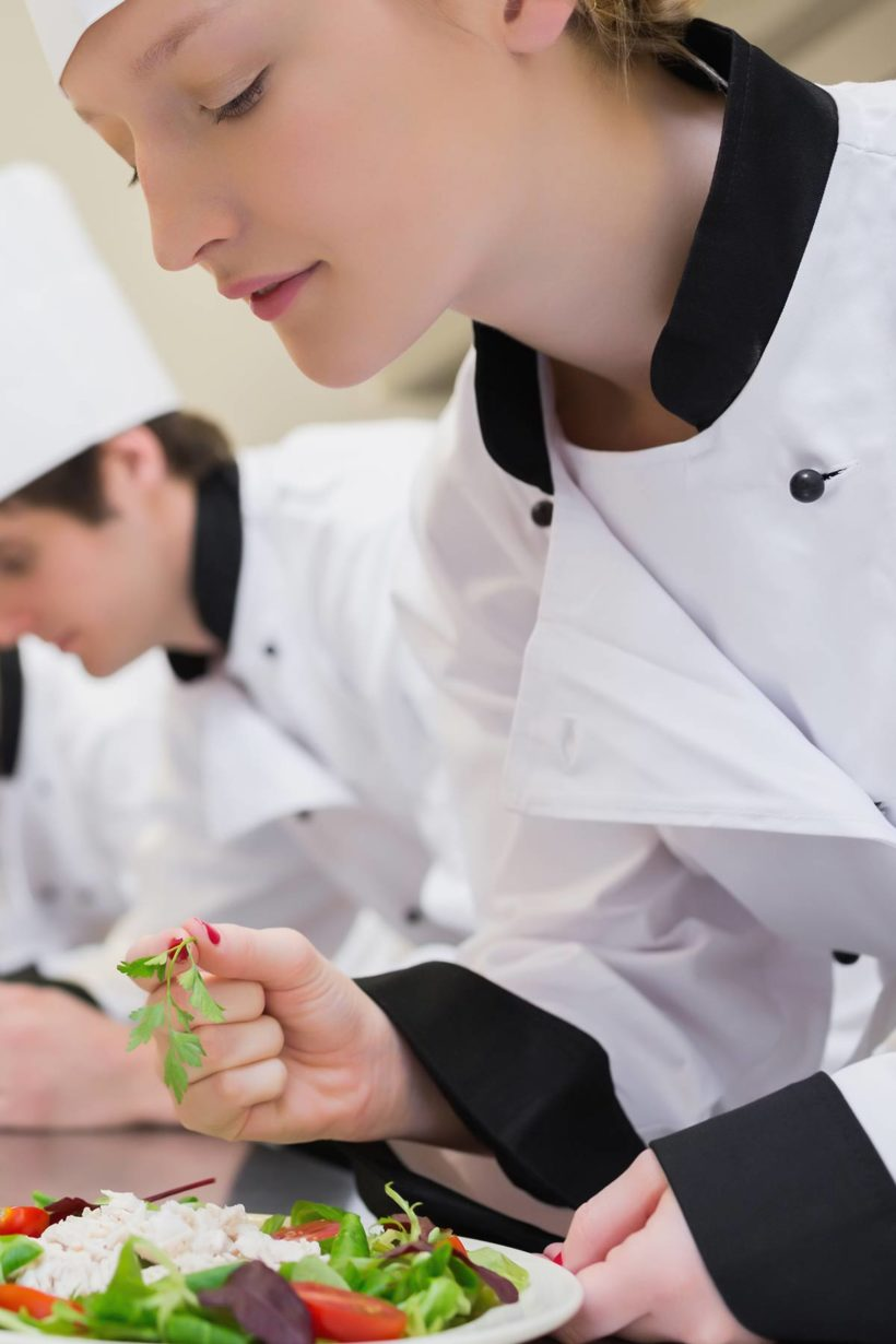 female culinary school student adding fresh herbs to a plated dish