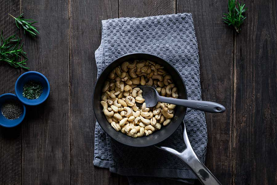 Raw cashews in a saucepan with olive oil