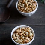 Rosemary salt and pepper cashews in two white bowls next to a wooden spoon
