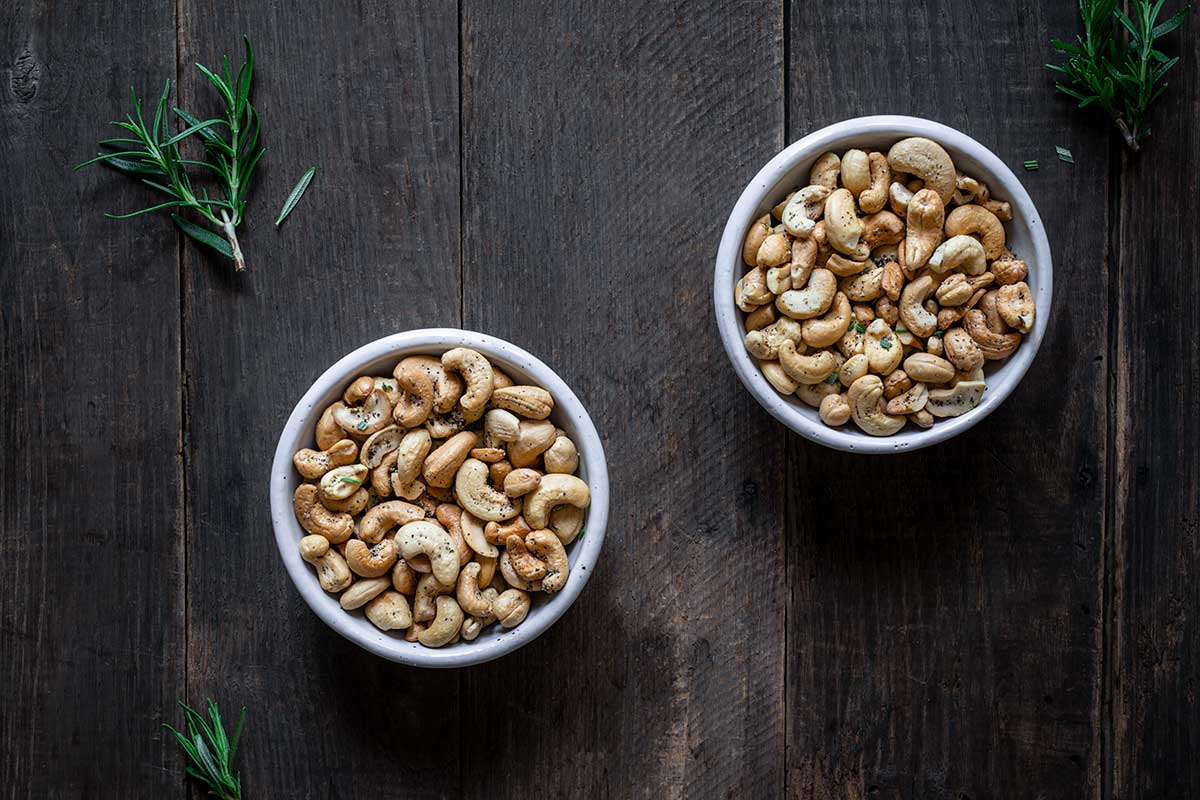 Rosemary salt and pepper cashews in two white bowls next to fresh rosemary