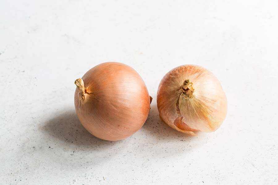 Two yellow onions on a white surface