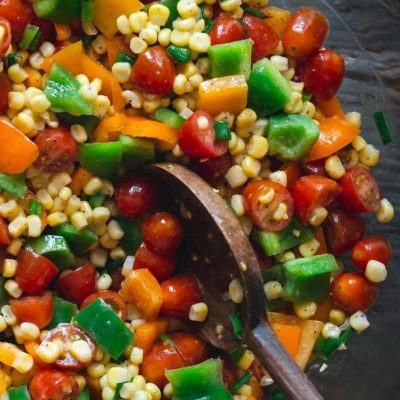 Corn salad in a grey bowl surrounded by bell peppers and tomatoes