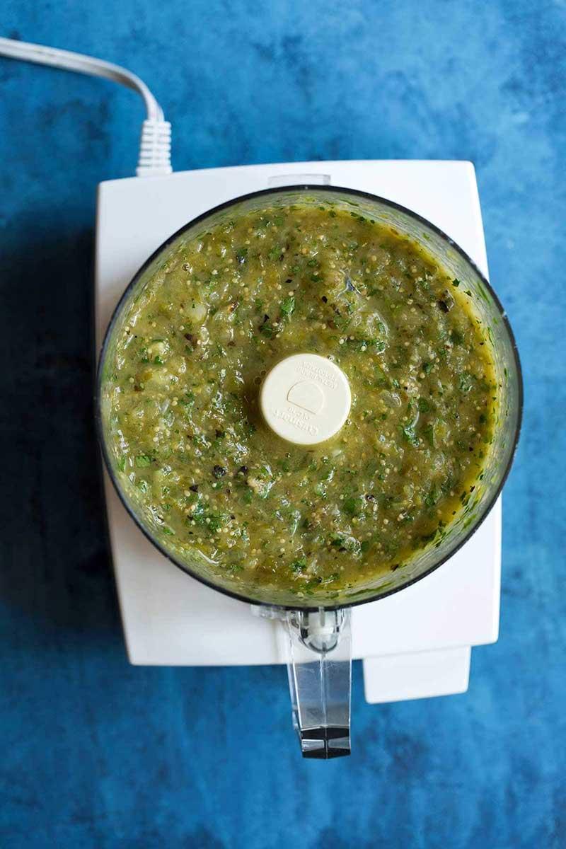Salsa verde in a food processor on a blue backdrop.