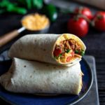 Closeup of breakfast burrito recipe with the end sliced off to show the filling