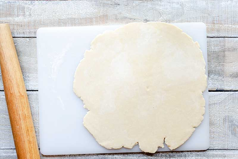 Rolled out tart dough next to rolling pin