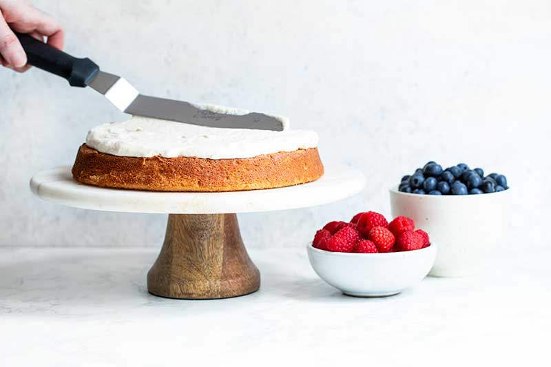 An offset spatula spreading cream cheese frosting over cake. Bowls of raspberries and blueberries sit nearby.