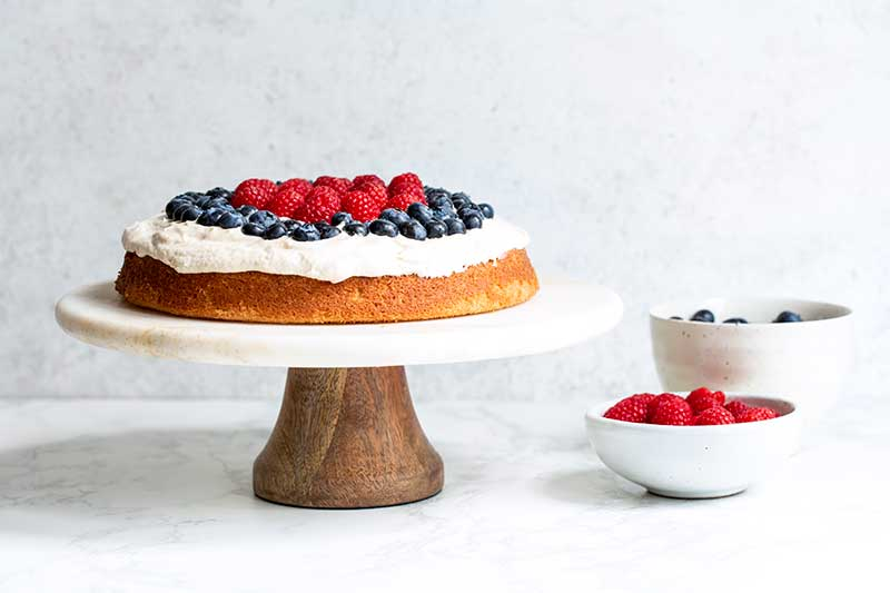 "The cake topped with both raspberries and blueberries for a ""red, white and blue cake"" effect."