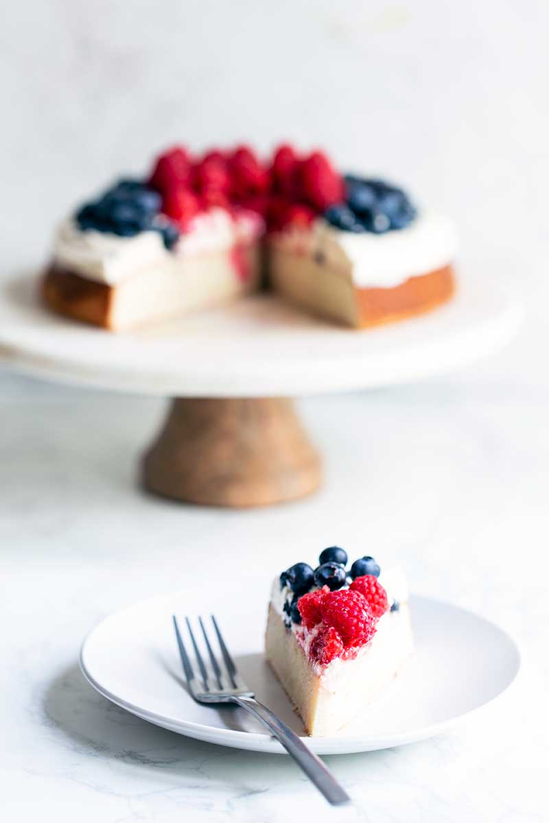 A slice of berry cake on a plate with a fork in front of the remaining cake