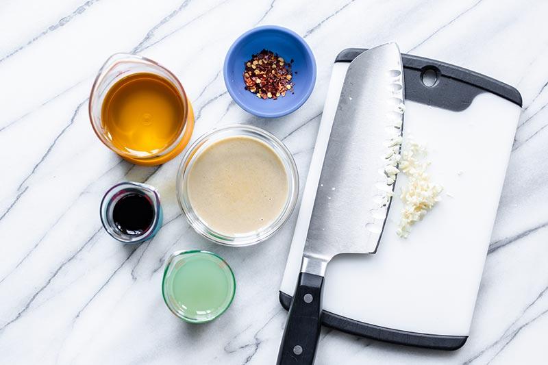 Ingredients for tahini dressing, including tahini, chopped garlic, red pepper flakes, lemon juice, and tamari