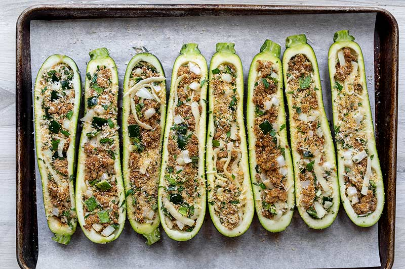 uncooked stuffed zucchini on a parchment lined sheet pan