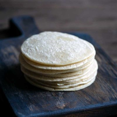 A stack of homemade corn tortillas on a cutting board
