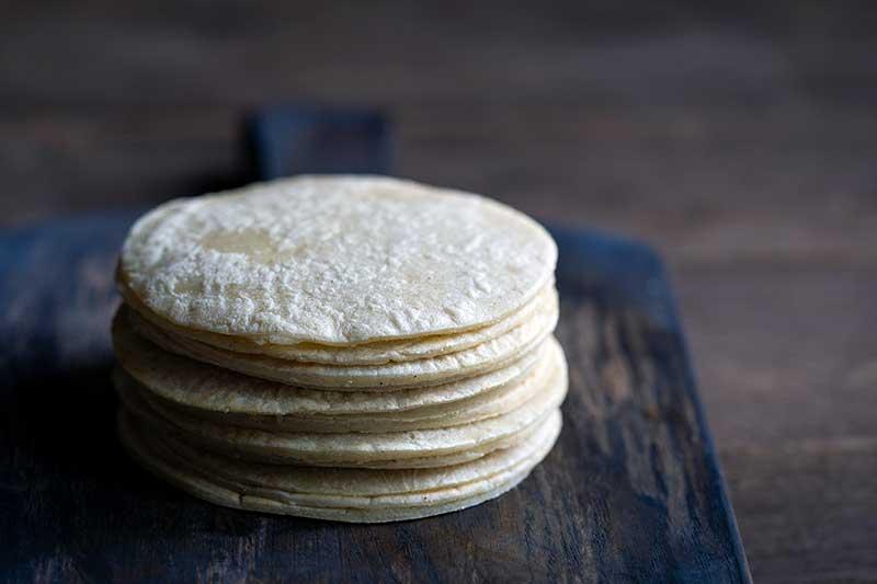 Homemade corn tortilla recipe stacked on a cutting board